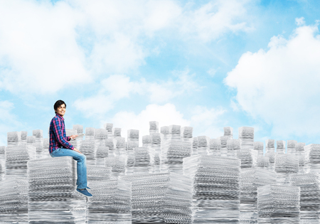 Young man in casual clothing sitting on pile of documents with cloudly skyscape on background. Mixed media. Imagens