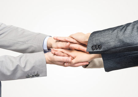 Close up of businesspeople putting their hands together against white background