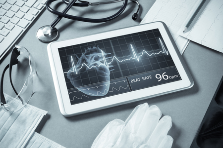 White tablet pc and doctor tools on gray surface Stok Fotoğraf