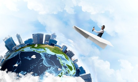 Pilot in leather helmet and goggles driving paper plane in cloudy blue sky. Funny man flying in small paper airplane over earth globe. Spherical view of modern city with high skyscrapers.