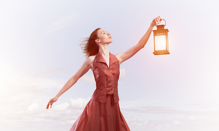 Young woman wearing dress with lantern against cloudy sky Standard-Bild - 120268775