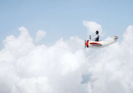 Man in aviator hat with goggles driving propeller plane. Funny man having fun in small airplane. Blue cloudy sky with fluffy clouds. Businessman sitting in paper plane and holding steering wheel.