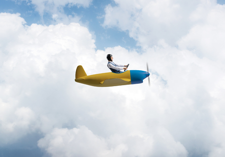Happy pilot driving small propeller plane on background of blue sky with clouds. Traveling around the world by airplane. Funny man flying in small airplane. Cloudscape background with fluffy clouds. Banco de Imagens
