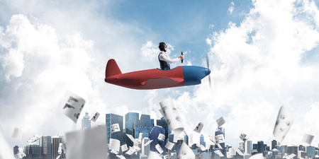 Business accounting and statistics concept with funny pilot. Aviator driving propeller plane above falling paper sheets with infographics. Young man flying in small airplane above paperwork. Stock Photo
