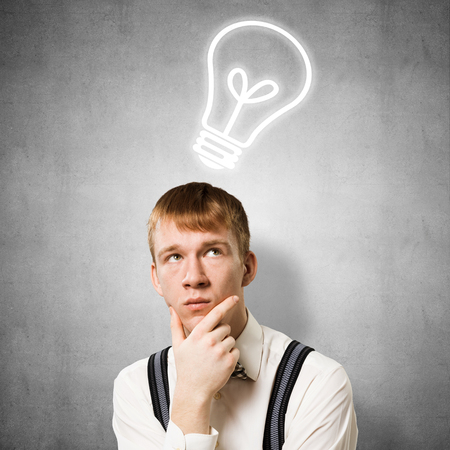 Redhead student thinking about some problem. Clever boy on background of grey wall with idea lightbulb sketch drawing overhead. Young businessman wears shirt and suspenders. New idea generation.