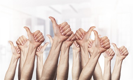 Row of man hands showing thumb up gesture. Agreement and approval group of signs. Human hands gesturing on light blurred background. Many arms raised together and present popular gesture. Foto de archivo