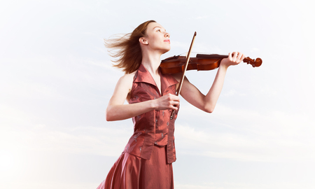 Young attractive girl playing violin over blue sky and cloud