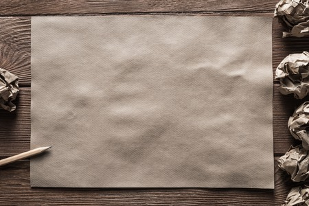 Crumpled brown paper sheet and pencil on wooden table Stock Photo - 120438222