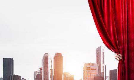 Main d'homme d'affaires ouvrant le rideau de velours rouge et le paysage urbain à l'arrière-plan