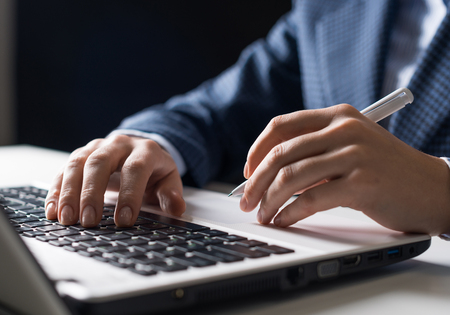 Man in business suit sitting at desk and working at laptop computer. Close-up of human hands holding pen and typing keyboard. Businessman at workplace in office. Business and digital technology Imagens - 120438291