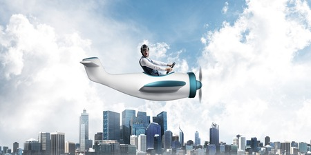 Businessman in aviator hat and goggles driving propeller plane above downtown with high modern buildings. Funny man having fun in small airplane. Blue sky landscape with clouds on background