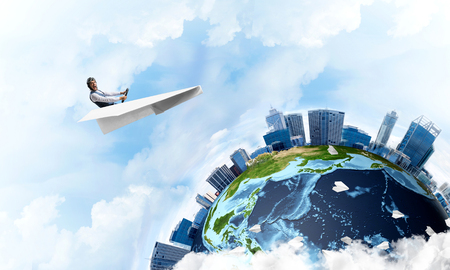 Funny aviator sitting in paper plane and holding steering wheel. Pilot driving paper plane in cloudy blue sky. Spherical view of modern city with high skyscrapers in business district.
