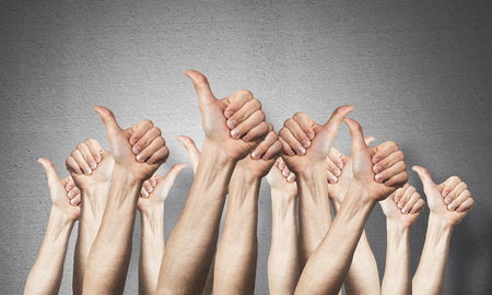 Row of man hands showing thumb up gesture. Agreement and approval group of signs. Human hands gesturing on background of grey wall. Many arms raised together and present popular gesture. Foto de archivo