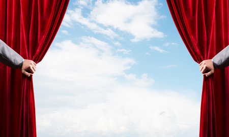 Human hand opens red velvet curtain on blue sky background Stock Photo - 120571062