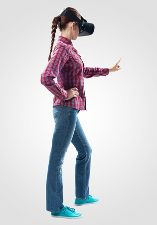 Beautiful girl using virtual reality glasses. Woman wearing VR goggles and interacts with cyberspace using pointing gesture. Studio photo by girl against gray background. Cyber technology concept