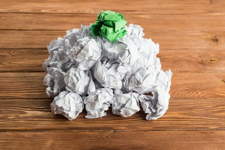 White crumpled up piece of paper on wooden table as idea Stock Photo