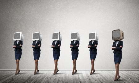 Business women in suits with monitors instead of their heads keeping arms crossed while standing in a row and one at the head with old TV in empty room against gray wall on background.