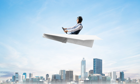 Businessman in aviator hat sitting in paper plane and holding steering wheel. Pilot driving paper plane above business center with high skyscrapers and office buildings. Cloudy blue sky background