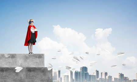 Young girl in superhero costume standing on building roof. Mixed media Stockfoto