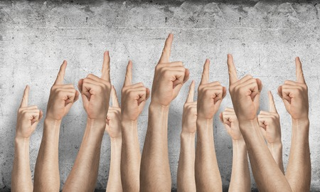 Row of man hands showing finger pointing gesture with forefinger. Group of human hands gesturing on background of grey wall. Many arms raised together and present popular gesture.