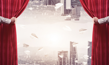 Hands of businessman opening red velvet curtain and cityscape Stock Photo