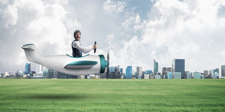 Happy aviator driving small propeller plane. Modern business center with high skyscrapers Stock Photo