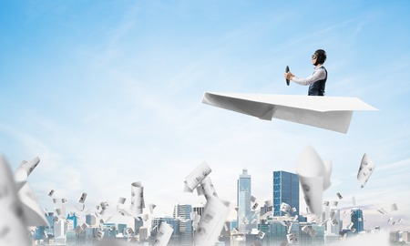 Businessman driving paper plane above business center in cloudy blue sky.