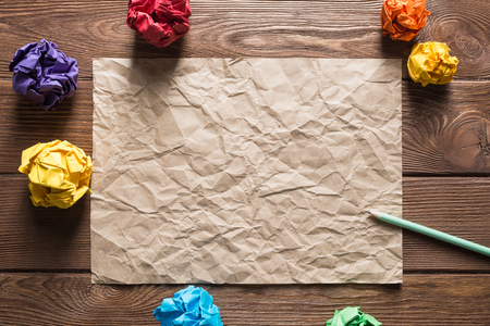 Crumpled brown paper sheet and pencil on wooden table Stock Photo - 120764257