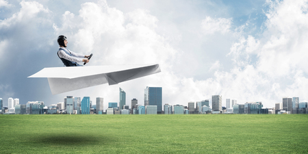Happy aviator driving paper plane. Modern business center with high skyscrapers on background. Man in paper airplane flying low above ground. Megalopolis panorama with green grass in sunny day