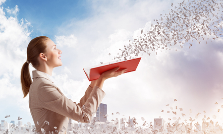 Woman looking at flying out random letters from opened book. Elegant young woman in white business suit holding open notebook on background of cityscape and cloudy blue sky. Business education concept