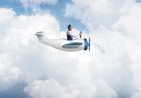 Happy pilot driving small propeller plane on background of blue sky with clouds. Traveling around the world by airplane. Funny man flying in small airplane. Cloudscape background with fluffy clouds. Stock Photo