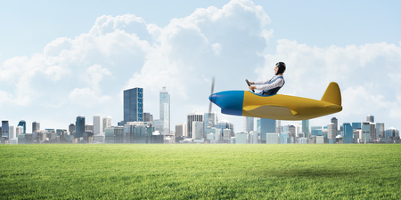 Businessman in aviator hat and goggles driving propeller plane. Downtown with high buildings. Man in airplane flying low above ground. Modern megalopolis panorama with green grass and cloudy sky Stok Fotoğraf