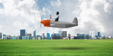 Businessman in aviator hat and goggles driving propeller plane. Downtown with high buildings. Man in airplane flying low above ground. Modern megalopolis panorama with green grass and cloudy sky Stock Photo