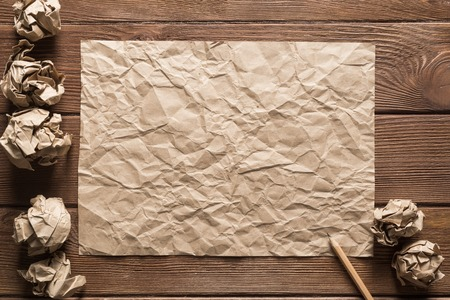 Crumpled brown paper sheet and pencil on wooden table Stock Photo - 120863247