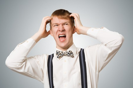 Stressful hipster screaming with panic and keeps hands on head. Emotional redhead boy has irritated facial expression. Portrait of guy wears white shirt, bow tie and suspenders on grey background Stockfoto
