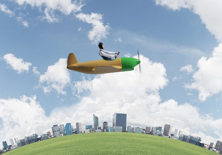 Happy businessman in leather helmet flying in propeller plane. Aviator driving small airplane above business center. Rounded city skyline with green grass, blue sky and modern office buildings.