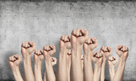 Row of man hands showing clenched fist gesture. Victory or protest group of signs. Human hands gesturing on background of grey wall. Many arms raised together and present popular gesture.