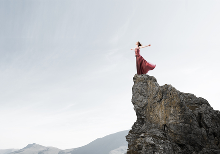 Young attractive woman relaxing in summer day standing on rock top