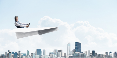 Aviator driving paper plane above megapolis. Side view of pilot sitting in paper plane and holding steering wheel. Cityscape with high skyscrapers and office buildings. Mixed media business concept