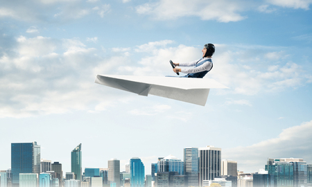 Aviator driving paper plane above business center in cloudy blue sky. Pilot in leather helmet sitting in paper plane and holding steering wheel. Cityscape with high skyscrapers and office buildings.