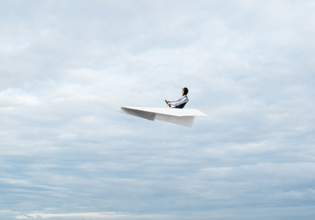 Businessman in aviator hat sitting in paper plane and holding steering wheel. Pilot driving paper plane in cloudy blue sky. Extreme aviation hobby. Sky panorama with fluffy clouds.