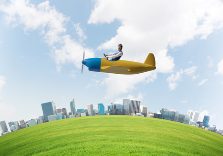 Screaming businessman in leather helmet flying in propeller plane. Emotional aviator driving small airplane above cityscape. Rounded city skyline with green grass, blue sky and modern skyscrapers Stock Photo