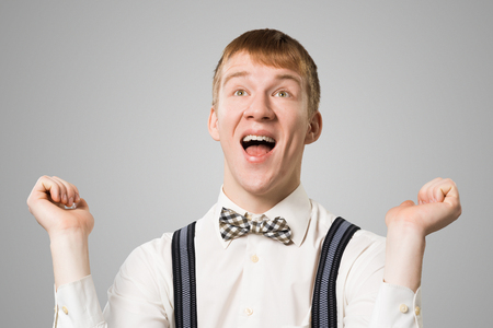 Friendly hipster smiling broadly with satisfied and pleasant look. Emotional redhead boy raising fists in hooray gesture. Portrait of guy wears white shirt, bow tie and suspenders on grey background