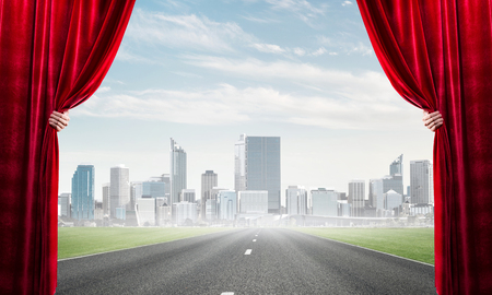 Human hand opens red velvet curtain to landscape with road Stock Photo - 121030825