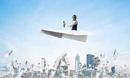 Screaming pilot sitting in paper plane and holding steering wheel. Aviator driving paper plane in blue sky above falling paper sheets with infographics. Cityscape with skyscrapers and office buildings Stock Photo