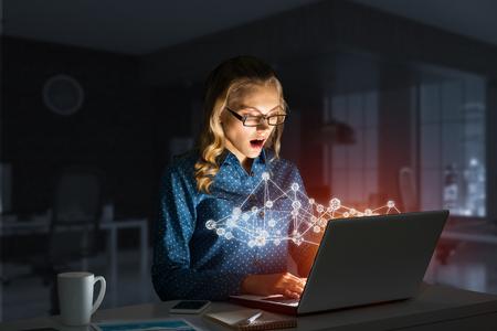 Surprised beautiful girl looking in glowing laptop screen. Mixed media Reklamní fotografie