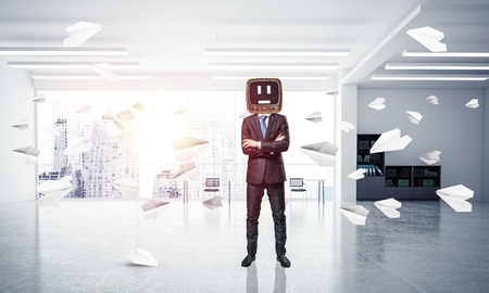 Businessman in suit with an old TV instead of head keeping arms crossed while standing among flying paper planes inside office building. 3D rendering.