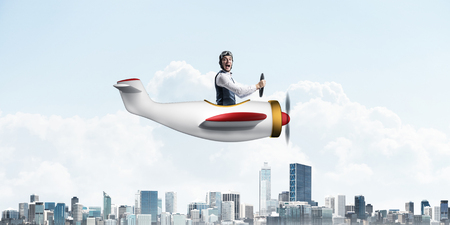 Business leadership and motivation concept with pilot sitting in cabin of small airplane. Funny man in aviator hat and goggles driving propeller plane above city. Modern megapolis with high buildings
