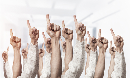 Row of man hands showing finger pointing gesture with forefinger. Group of human hands gesturing on light blurred background. Many arms raised together and present popular gesture. Stock Photo