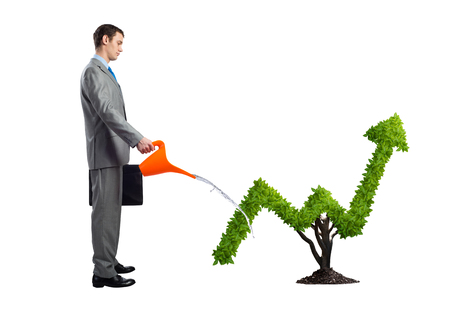 Businessman watering green plant in shape of grow up trend isolated on white background. Business analytics and statistics. Friendly ecosystem for business. Business growth and development.